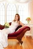 Retrato de la novia que se sienta en el sofá de desfallecimiento por la ventana fotografía de archivo