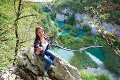 Retrato de la opinión de Aeirial de la mujer turística sonriente joven que se sienta en piedra, mostrando los pulgares para arrib fotografía de archivo