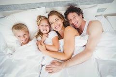 Retrato de la opinión de alto ángulo de la familia feliz que se relaja en cama foto de archivo