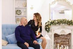 Retrato de la pareja casada contra el cual presenta y se sienta en el sofá Foto de archivo