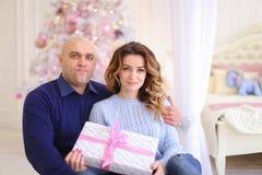 Retrato de la pareja casada contra el cual presenta y se sienta en piso Imágenes de archivo libres de regalías