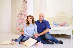 Retrato de la pareja casada contra el cual presenta y se sienta en piso Fotos de archivo