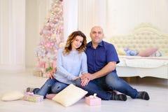 Retrato de la pareja casada contra el cual presenta y se sienta en piso Fotos de archivo libres de regalías