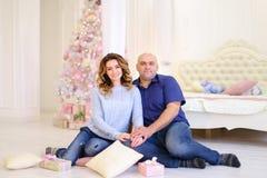 Retrato de la pareja casada contra el cual presenta y se sienta en piso Imagenes de archivo
