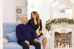 Retrato de la pareja casada contra el cual presenta y se sienta en el sofá Foto de archivo libre de regalías