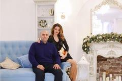 Retrato de la pareja casada contra el cual presenta y se sienta en el sofá Imagen de archivo libre de regalías