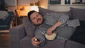 Retrato de la película de observación del hombre atractivo en la TV en el apartamento acogedor de la noche en casa metrajes