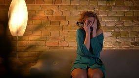 Retrato de la película de terror de observación asustada y de ocultar de la muchacha caucásica rizado-cabelluda del jengibre su c almacen de metraje de vídeo