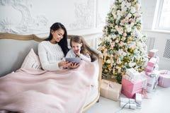 Retrato de la pequeña hija sonriente que se sienta así como su madre y que usa la tableta digital en casa en el tiempo de la Navi fotos de archivo libres de regalías