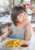 Retrato de la pequeña muchacha asiática en restaurante de los alimentos de preparación rápida fotografía de archivo