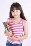 Retrato de la pequeña muchacha asiática que sostiene el libro encendido aislado en el fondo blanco Foto de archivo