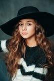 Retrato de la pequeña muchacha de la moda hermosa en sombrero en fondo del vintage Foto de archivo