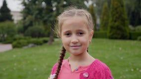 Retrato de la pequeña muchacha sonriente que mira la cámara almacen de video