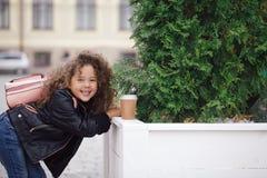 Retrato de la pequeña muchacha sonriente rizada del inconformista en chaqueta con café Estilo urbano Otoño outdoor Fotografía de archivo