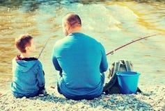 Retrato de la pesca del padre y del hijo con las barras Imagen de archivo libre de regalías