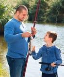 Retrato de la pesca del padre y del hijo con las barras Imágenes de archivo libres de regalías