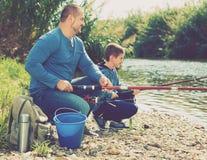 Retrato de la pesca del padre y del hijo con las barras Fotos de archivo libres de regalías