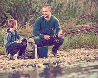 Retrato de la pesca del padre y del hijo con las barras Imagenes de archivo