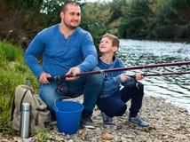 Retrato de la pesca del padre y del hijo con las barras Foto de archivo libre de regalías