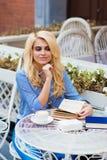 Retrato de la preparación femenina del estudiante encantador joven para las conferencias mientras que se sienta en cafetería al a Imágenes de archivo libres de regalías