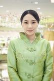 Retrato de la presentadora sonriente del restaurante/del hotel en ropa del chino tradicional en el restaurante Imagenes de archivo