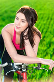 Retrato de la puesta del sol de la mujer y en la bici Fotografía de archivo libre de regalías