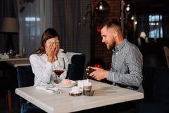 Retrato de la recepción feliz y sorprendida de la mujer joven presente de novio mientras que se sienta en café imagen de archivo