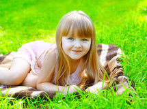 Retrato de la reclinación de mentira sonriente linda del niño sobre la hierba Imágenes de archivo libres de regalías