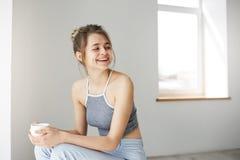 Retrato de la risa sonriente de la muchacha feliz alegre joven sosteniendo la taza que se sienta en silla sobre la pared blanca e Fotos de archivo libres de regalías