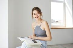 Retrato de la risa sonriente de la muchacha feliz hermosa joven sosteniendo el libro que mira la cámara que se sienta en silla so Fotografía de archivo libre de regalías