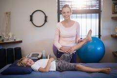 Retrato de la rodilla de examen sonriente del terapeuta de sexo femenino joven con el muchacho que miente en cama foto de archivo libre de regalías