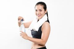 Retrato de la ropa del deporte de la mujer que lleva joven y del agua potable Imagen de archivo
