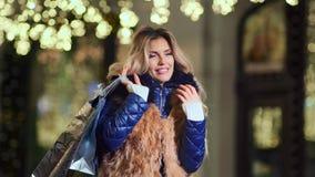 Retrato de la ropa sonriente de la piel de la mujer del encanto que lleva que sostiene los regalos de los bolsos de compras que m almacen de video