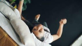 Retrato de la señora asiática feliz en el balanceo blanco de la camiseta en cama, sonriendo y mirando la cámara que expresa emoci metrajes