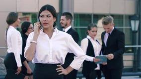 Retrato de la señora atractiva del negocio que hace una llamada de teléfono importante y sus colegas que se colocan detrás y char almacen de metraje de vídeo