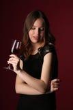 Retrato de la señora en vestido negro con el vino Cierre para arriba Fondo rojo oscuro Foto de archivo