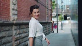 Retrato de la señora joven alegre que camina entonces dando vuelta a mirar la sonrisa de la cámara almacen de metraje de vídeo