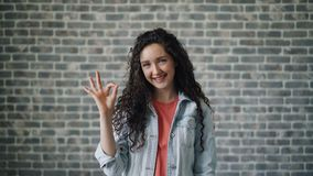 Retrato de la señora joven alegre que muestra el gesto de mano ACEPTABLE que sonríe mirando la cámara almacen de metraje de vídeo