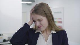 Retrato de la se?ora joven cansada triste en la ropa formal que mira in camera La mujer con el pelo largo ten?a dolor de cabeza,  almacen de video