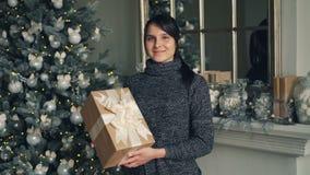 Retrato de la señora joven encantadora con la situación de la caja de regalo cerca del árbol de navidad y la mirada adornada de l almacen de metraje de vídeo