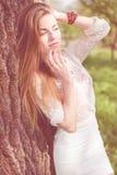 Retrato de la señora joven rubia hermosa que se divierte que presenta en el árbol que sonríe y que mira sensual suavemente el esp Imágenes de archivo libres de regalías