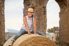 Retrato de la sentada adolescente alegre feliz en pajar Foto de archivo