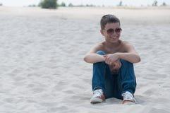 Retrato de la sentada adolescente en la arena Fotos de archivo
