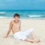 Retrato de la sentada adolescente en la arena cerca del mar Imagen de archivo libre de regalías