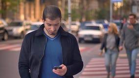 Retrato de la situación caucásica del hombre en paso de peatones y de la observación en smartphone con la gente que camina borros almacen de metraje de vídeo