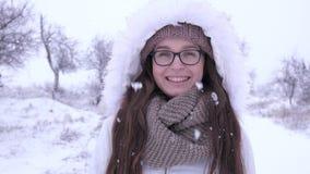 Retrato de la situación con gafas femenina preciosa bajo nevadas en invierno almacen de metraje de vídeo