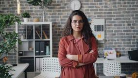 Retrato de la situación femenina bonita del empresario en oficina con los brazos cruzados