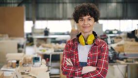 Retrato de la situación hermosa del carpintero de la mujer en taller con los brazos cruzados almacen de video