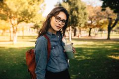 Retrato de la situación hermosa de la mujer en el parque con el zumo de fruta Camisa y lentes femeninas del dril de algodón que l imagen de archivo