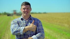Retrato de la situación masculina feliz del hombre del granjero en el campo del centeno de la avena del trigo de la granja orgáni almacen de metraje de vídeo
